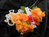 Orange flowers, white paper and white diamonds on black background — Stock Photo