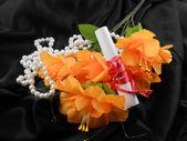 Flores naranjas, papel blanco y diamantes blancos sobre fondo negro — Foto de Stock