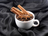 Composition with white cup of coffee, coffee beans and cinnamon — Stock Photo