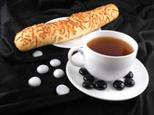 Hot coffee with bread and stones on black background — Stock Photo