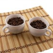 Coffee beans, coffee cup on bamboo background — Stock Photo