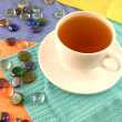 Outdoor cup of tea in a white cup with stones on a material background — Foto de Stock