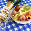 Kiwi tasty cake close up at plate, champagne bottle, diamonds and christmas balls — Stock Photo