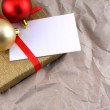 Golden gift box with red ribbon, christmas balls and empty card — Stock Photo