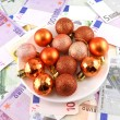 Christmas balls set on white plate, dollar background — Stock Photo