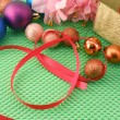 Beautiful flowers, gifts and Christmas balls on green background — Стоковая фотография
