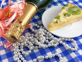 Kiwi tasty cake close up at plate, champagne bottle and flowers — Stock Photo