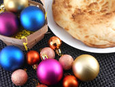 Christmas cake on white plate and christmas baubles — Foto Stock