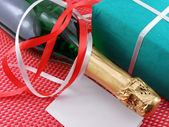 Bottle of a champagne and green gift boxes — Stock Photo