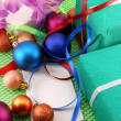 A gift box with a white ribbon and new year balls — Стоковая фотография