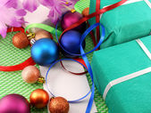 A gift box with a white ribbon and new year balls — Stock Photo
