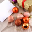 Golden gift box with red bow and christmas balls set on old paper — Stock Photo #36942917