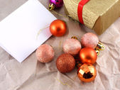 Golden gift box with red bow and christmas balls set on old paper — Stock Photo