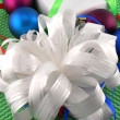 Christmas balls, white gift box and holiday bow — Stock Photo