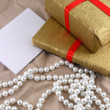 Golden gift box with red bow with pearls on old paper — Stock Photo