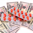 Medical pills on dollars bank note as symbol for high costs — Stock Photo