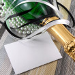 Champagne bottle with christmas present, holiday invitation card — Stock Photo