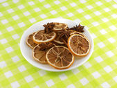 Old lemon slices and cinnamon on white plate — Stock Photo