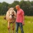 A man walks with his horse — Stock Photo