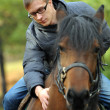 Young man on a horse — Stock Photo