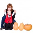 Baby boy in black halloween costume with pumpkins — Stock Photo #12556438