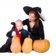 Baby boy in black halloween costume with pumpkins — Stock Photo #12556443