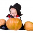 Baby boy in black halloween costume with pumpkins — Stock Photo #12556449