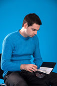 Man in a blue jersey with a notebook — Stock Photo