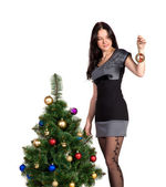 Brunette girl decorates the Christmas tree balls — Stock Photo