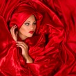 Sensual face  in red satin fabric — Stock Photo