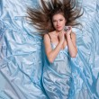 Girl with long hair lying on blue silk fabrics — Stock Photo