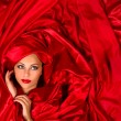 Sensual face in red satin fabric — Stock Photo #17415541