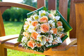 Wedding bouquet on wooden chair — Stock Photo