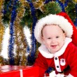 Little baby boy wearing Santa's costume sitting and holding a box with — Stock Photo #8085063
