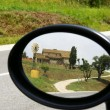 Stock Photo: Farmhouse reflected in a rear-view mirror of a car