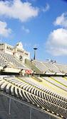 Harrow seats under the arch and the clock in Montjuïc's olympic stadium, Barcelona — Stock Photo