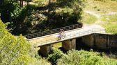Cyclist on a bridge on the river Foix — Stock Photo