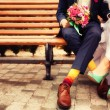 Foto Stock: Bride and groom in bright clothes on bench
