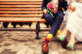 Bride and groom in bright clothes on the bench — Stockfoto