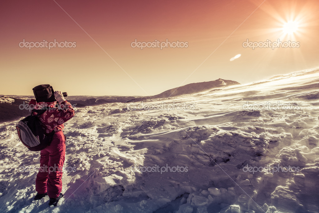 Tourist looking through binoculars on the snowy slopes of the Carpathian Mountains — Stock Photo #18568509