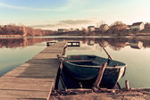 Old fishing boat ashore lake — Stock Photo