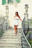 Beautiful woman stepping down stair — Stock Photo