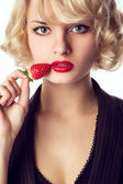 Woman eating a strawberry — Stockfoto