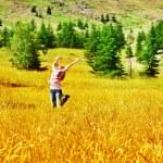 Girl jumping on wheat field — Stock Photo