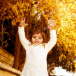 Small girl in autumn backyard - Stock Photo