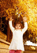 Small girl in autumn backyard — Stock Photo
