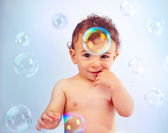 Cute baby boy playing with soap bubbles — Stock Photo