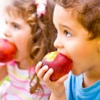 Happy children eating apple — Stock Photo