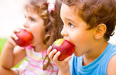 Happy children eating apple — Stok fotoğraf