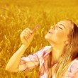 Girl blowing soap bubbles on wheat field — Stock Photo